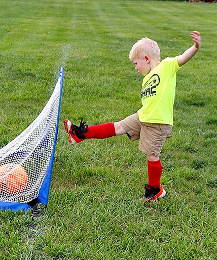Kid kicking soccer ball into goal