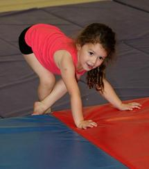 Girl performing gymnastic maneuver on a mat