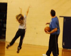 A girl shooting a basket at a basketball camp